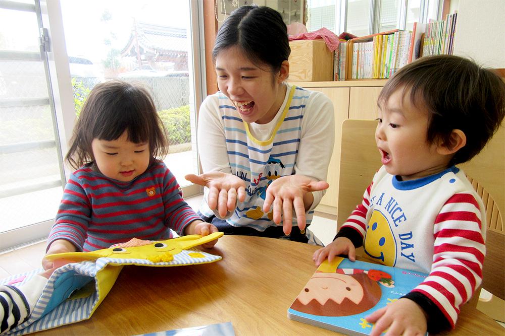 先生と一緒に絵本を読む子どもたち