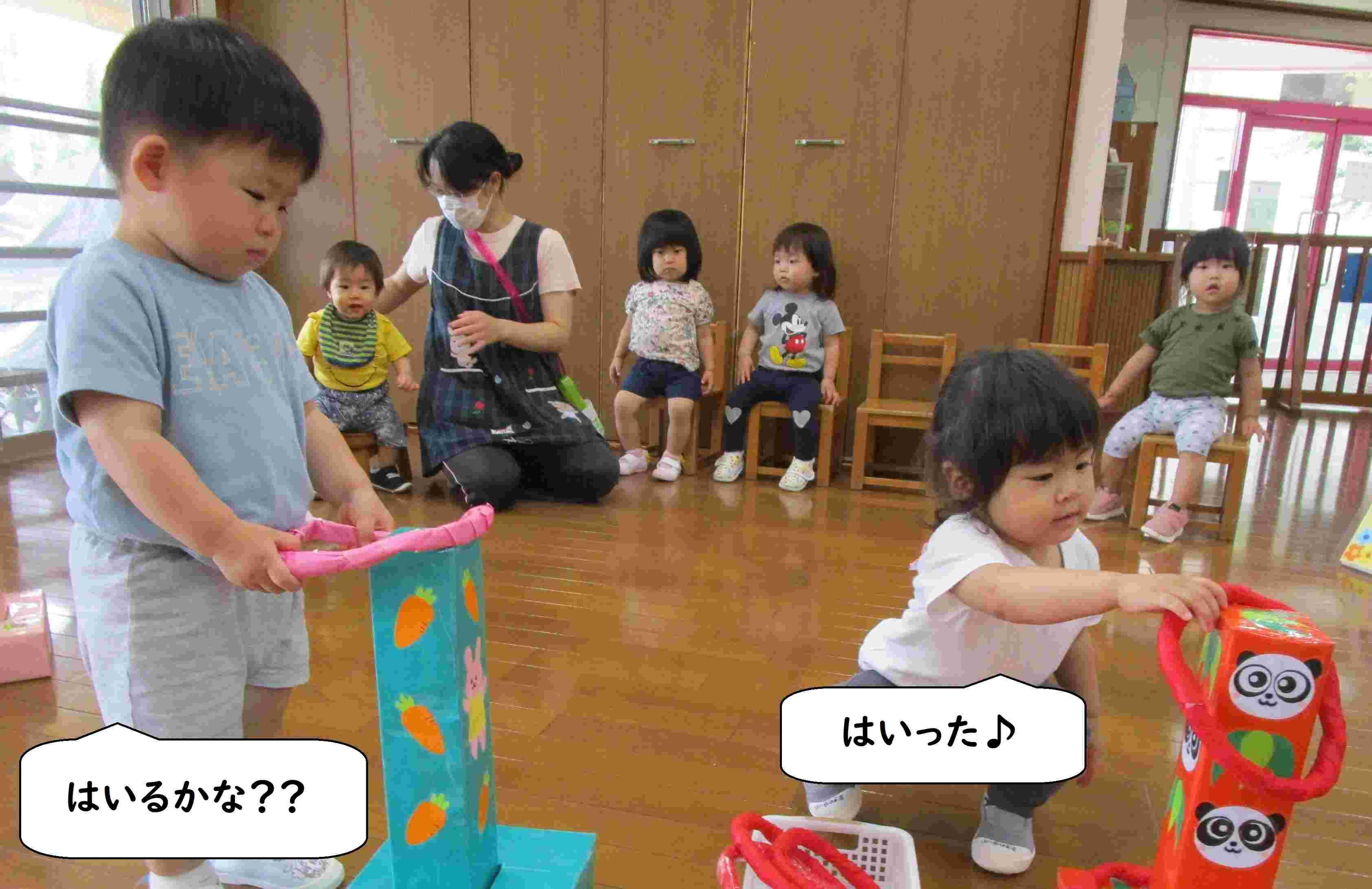わなげをする男の子と女の子 その後ろで順番を待つ一歳児