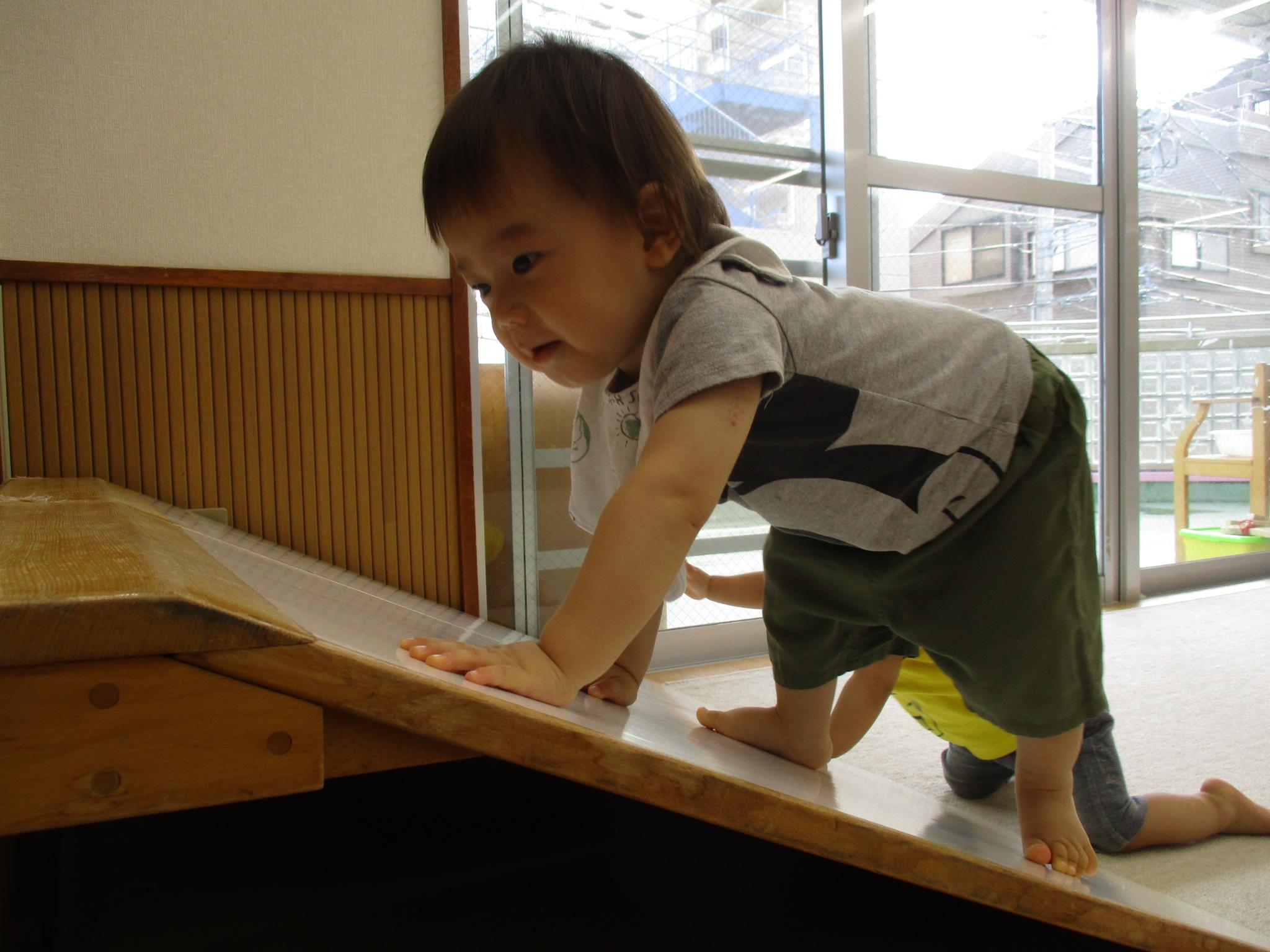 滑り台の斜面をのぼる男の子
