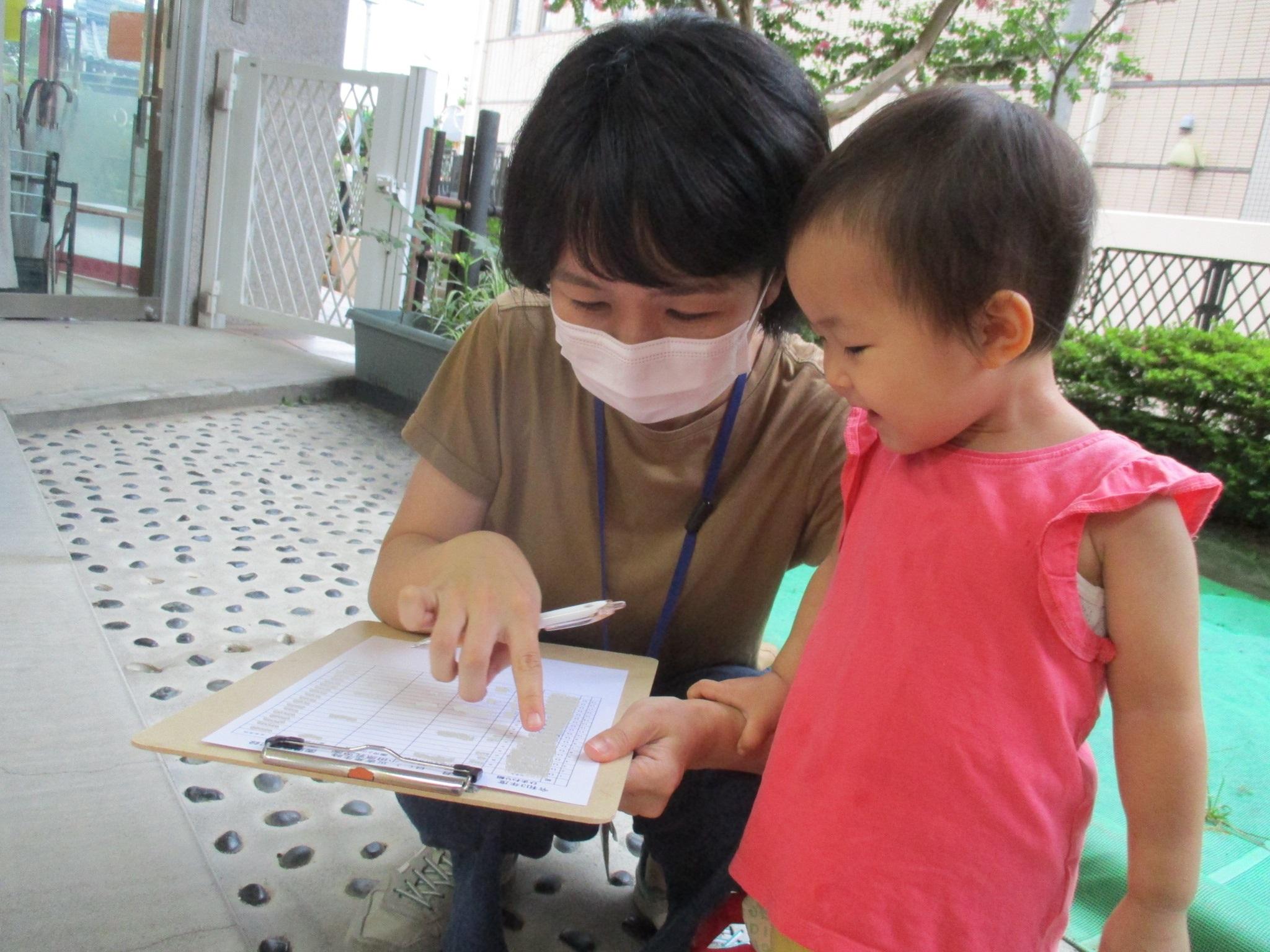 災害時引き渡し名簿に記入する保護者 それを見守る子ども